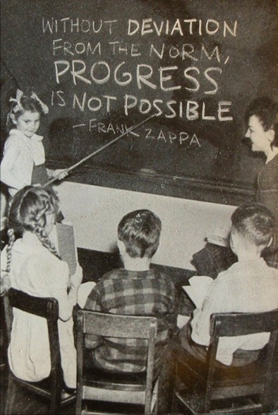 "A teacher and 4 children looking at a blackboard on which is written ""Without deviation from the norm, progress is not possible"""